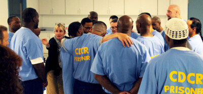Group of men and Fritzi stepping inside the circle with arms around eachother