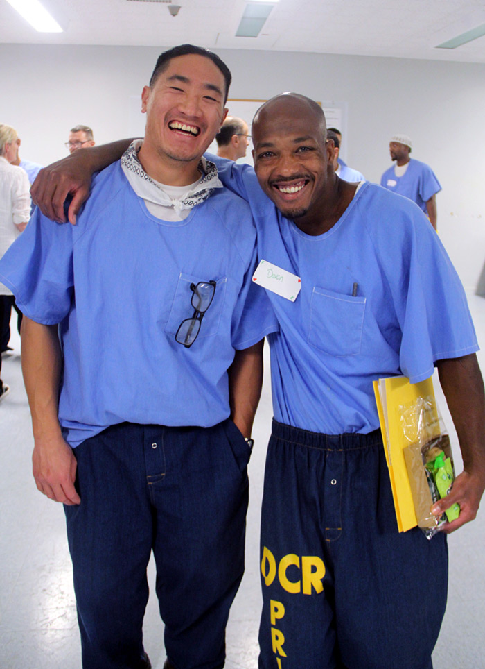 One Asian and one African American incarcerated men with arms around eachother smiling