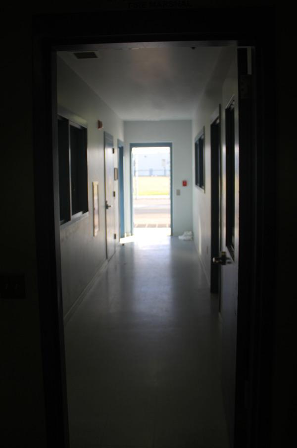 Open door to outside from inside dark hallway
