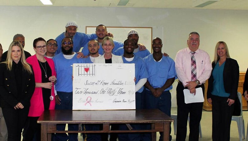 Group of incarcerated men and CPP volunteers with big check for breast cancer fundraiser