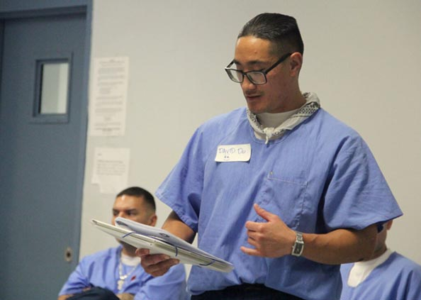 Incarcerated man standing up reading to group of people