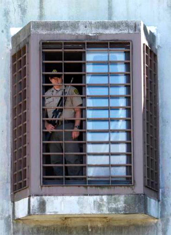 Correctional officer with weapon looking out barred window from a prison