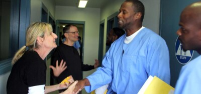 Woman shaking hands with incarcerated male with excited happy expression