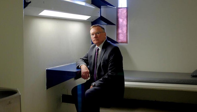 Rick Raemisch sitting in a solitary confinement cell