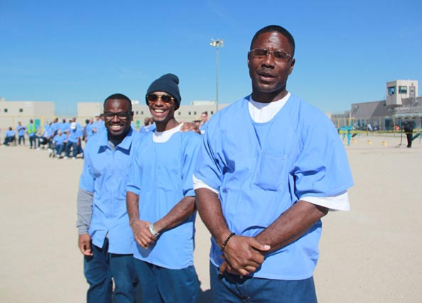 Three incarcerated men standing outside smiling