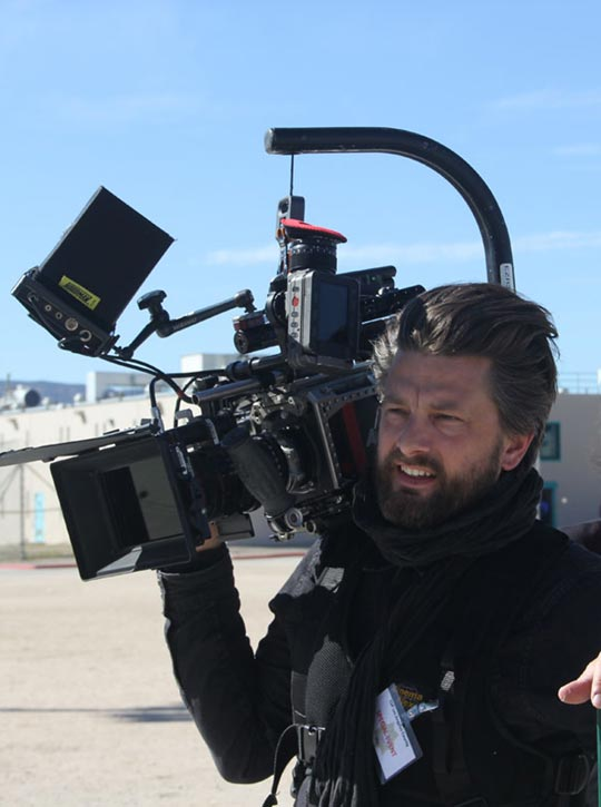 Videocamera man on the set of Step Inside The Circle smiling