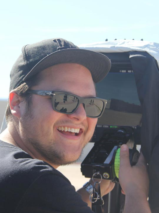 Videocamera man wearing sunglasses on the set of Step Inside The Circle smiling