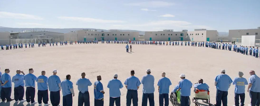 Woman with microphone standing in middle of circle of 235 incarcerated men