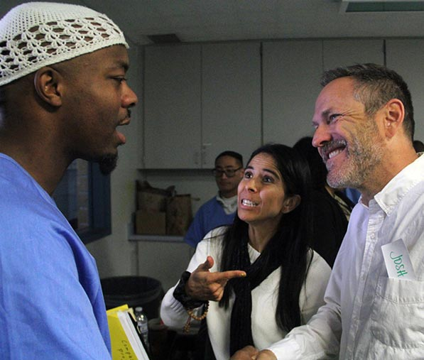 Smiling man and woman shaking hands and talking to incarcerated man in prison