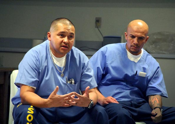 Two incarcerated men sitting down talking