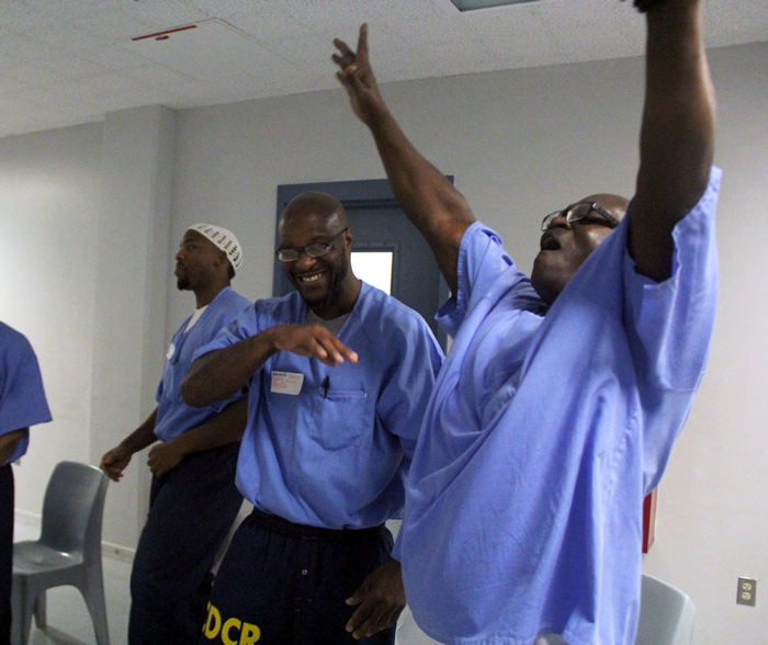 Incarcerated man with hands in the air celebrating