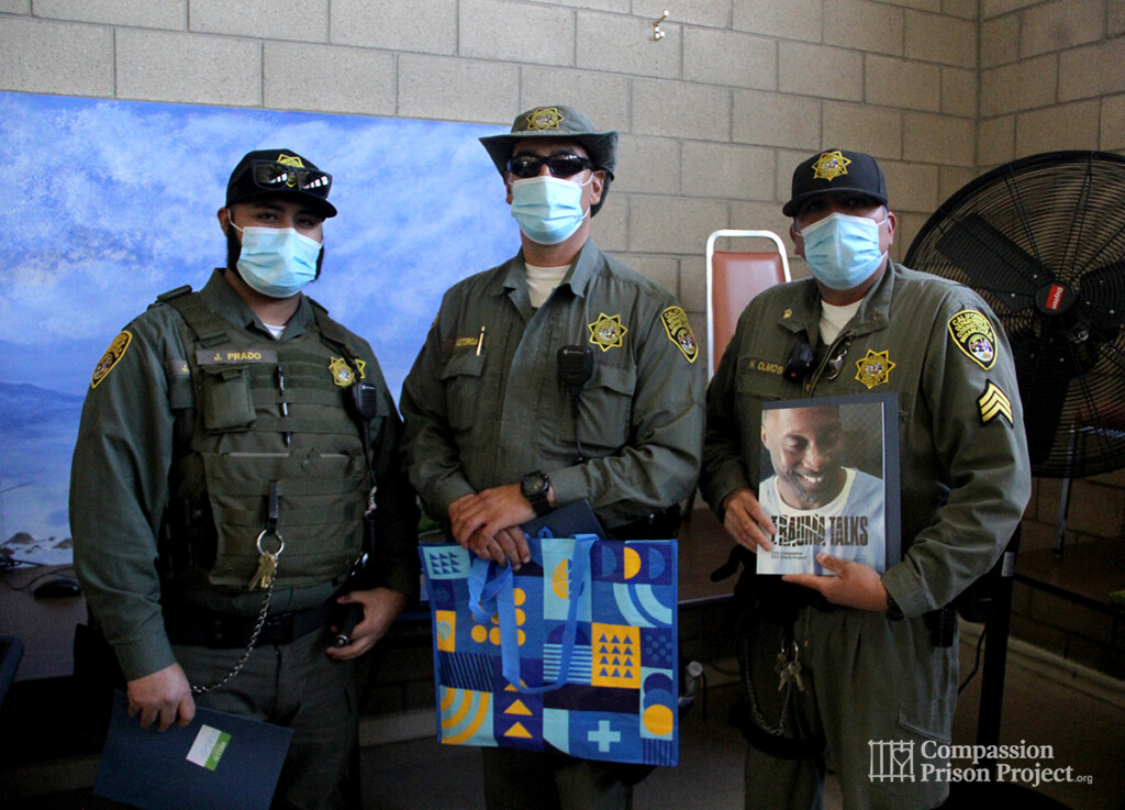 3 correctional officers holding Trauma Talks workbook and bag