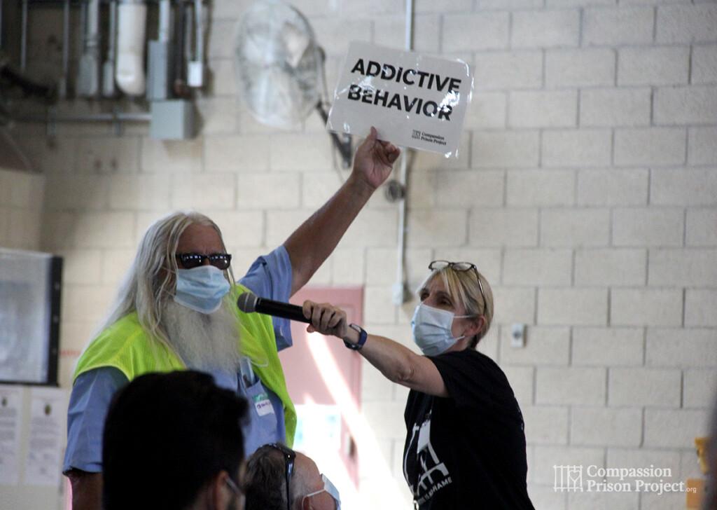 Man holding up sign that says 'addictive behavior'