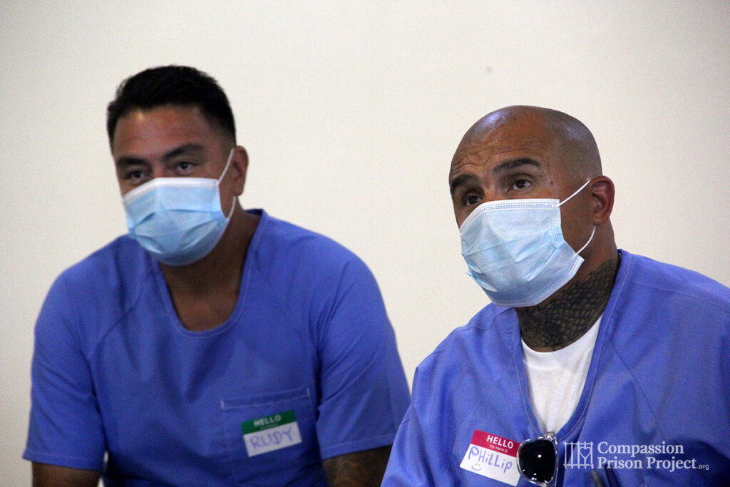 Two men sitting in masks