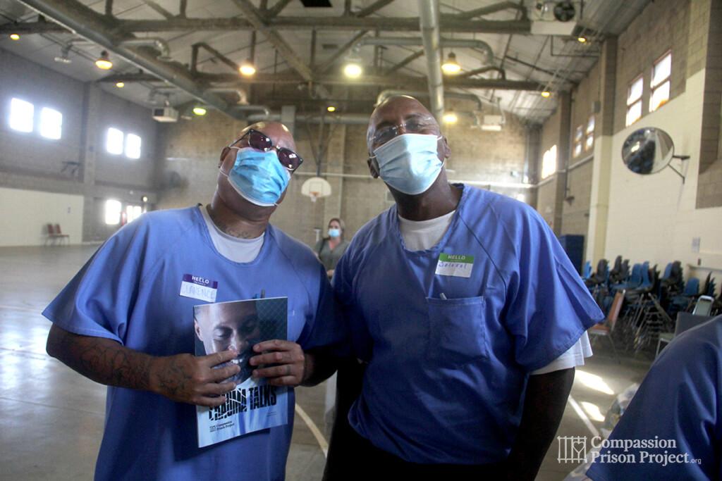 2 men in masks holding our workbook Trauma Talks