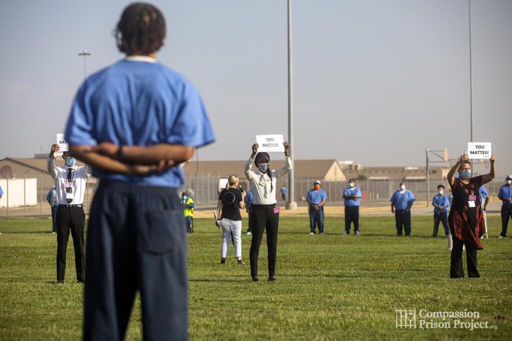 Nadine Burke Harris holding up 'you matter' sign infront of men living in prison