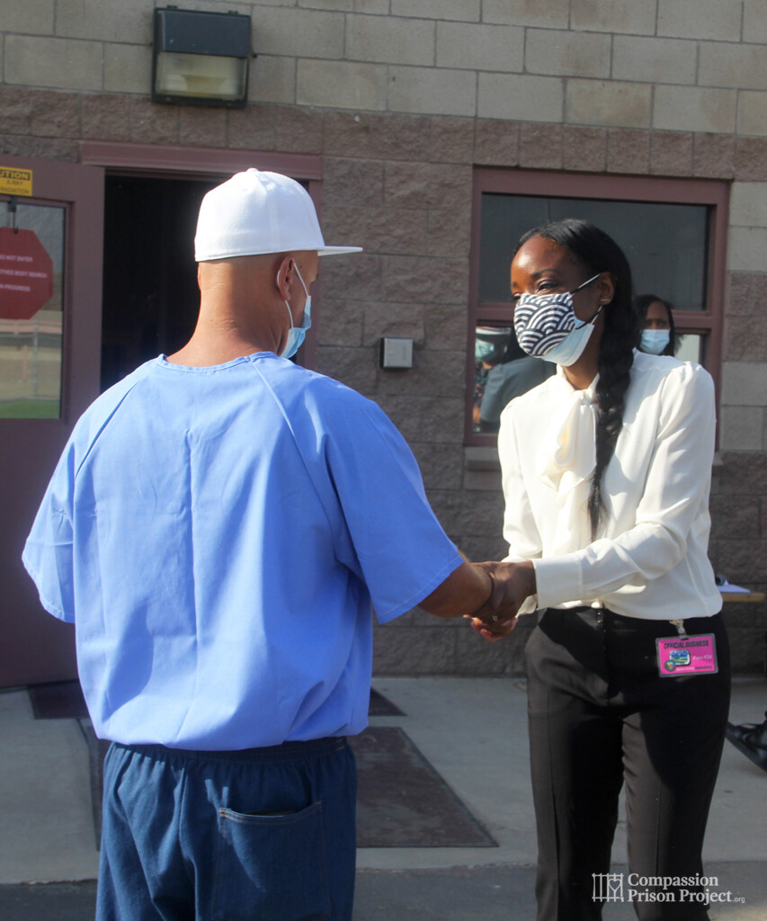 Nadine Burke Harris shaking hand of young man in prison